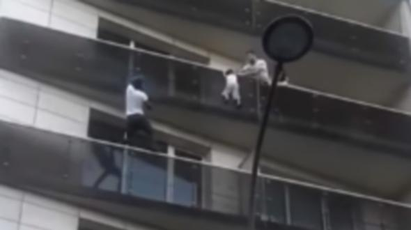 mann rettet von balkon h ngendes kleinkind. Black Bedroom Furniture Sets. Home Design Ideas