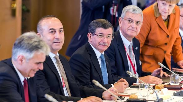 Der türkische Premierminister Ahmet Davutoglu (Mitte) steht beim EU-Sondergipfel in Brüssel im Mittelpunkt; links im Bild der österreichische Kanzler Werner Faymann, ganz rechts die deutsche Kanzlerin Angela Merkel.